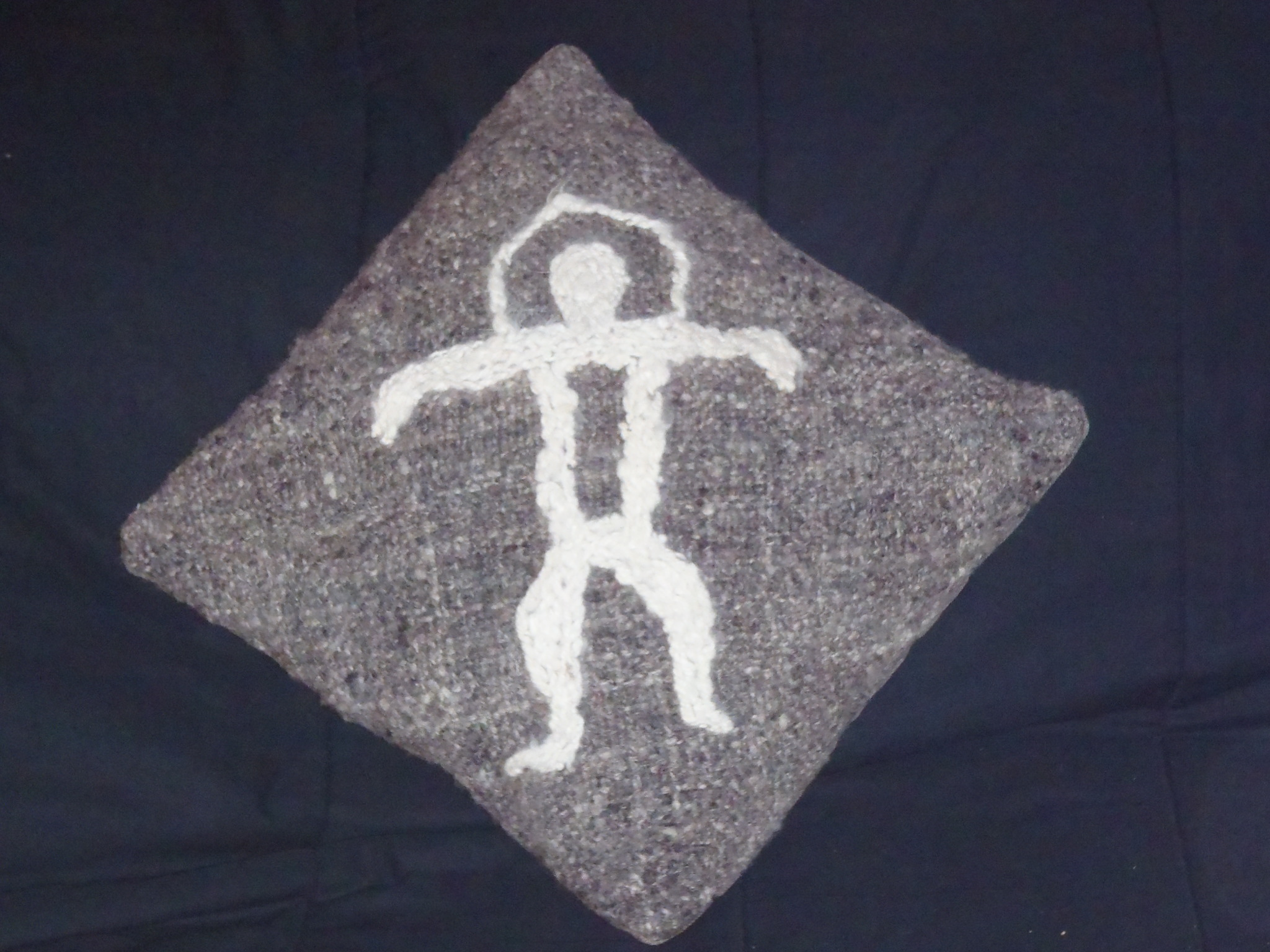 Wool filled cushion with woven wool cover with rainbow man petroglyph on it.